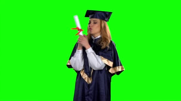 Graduate holding a diploma and kisses him. Green screen. Slow motion