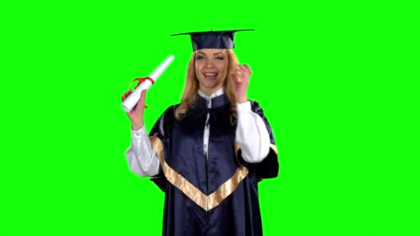 Woman graduate in gown with diploma. Green screen. Slow motion