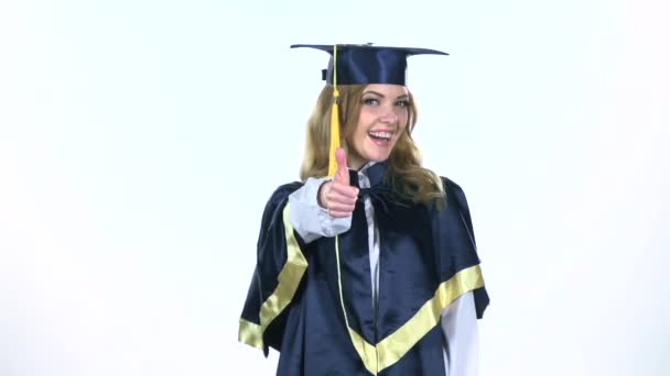 Graduate showing thumbs up and winking eyes. White. Slow motion