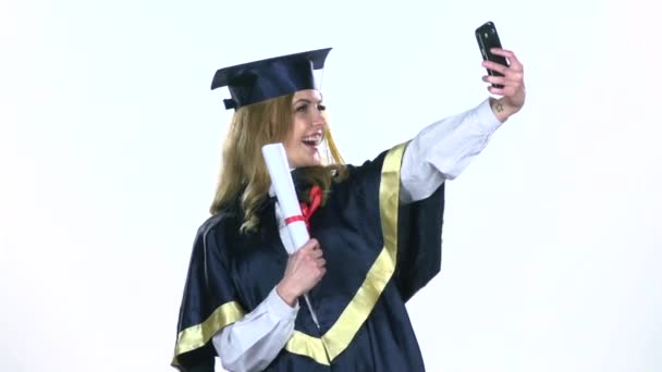 Female graduate makes selfie photo with diploma. White. Slow motion