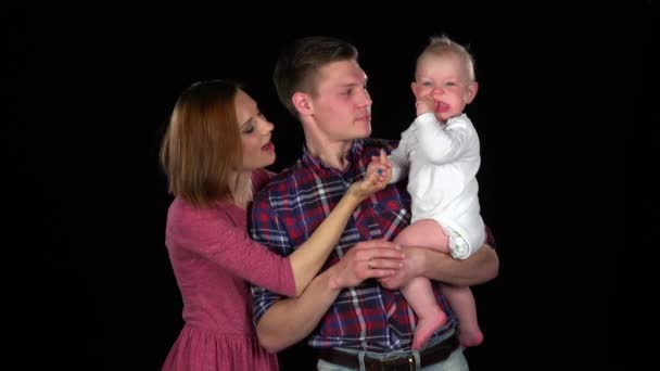 Video of happy family of three people. Father, mother, baby playing. Black
