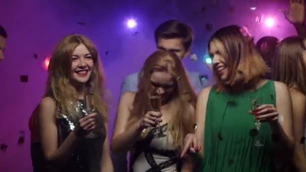 Fiatal lányok tánc- és beszélgetés-val pohár pezsgő