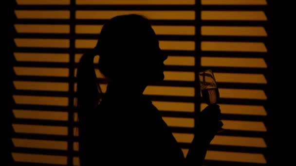 Girl drinking white wine with glasses. Silhouette. Close up
