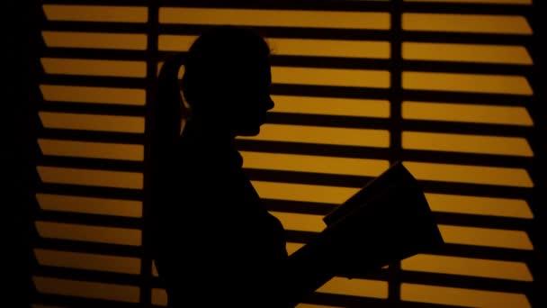 Mädchen blättert in einem Buch. Buch in den Händen. Silhouette. Nahaufnahme