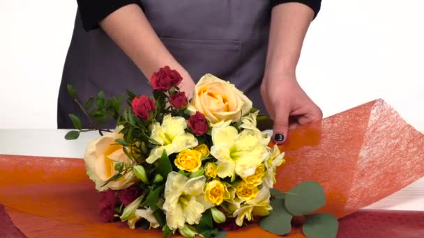 Florist does a wrap for bouquet flowers. White. Slow motion. Close up