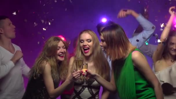 Close-up of girls clinking glasses and drinking champagne. Slow motion