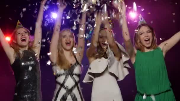 Giovani ragazze gettando coriandoli glitter e danzante divertimento