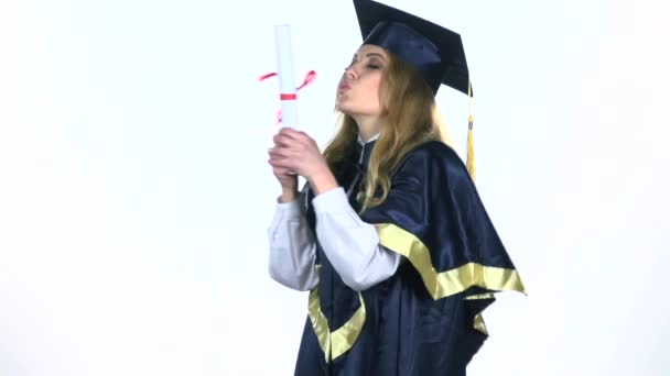 Graduate celebrates the end of the college in kissing her diploma. White. Slow motion