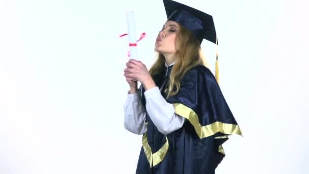 Absolventka slaví konec školy v líbat její diplom. Bílá. Zpomalený pohyb