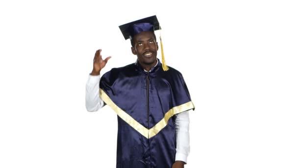 Graduate picks up square academic cap and throws. White
