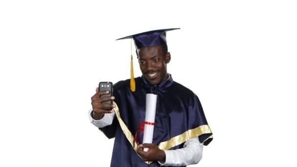 Absolventi si vezme fotku s diplomem. Bílé