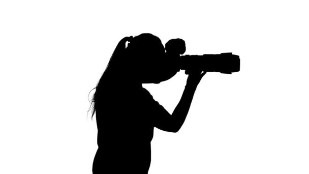 Photographer is holding the camera and takes photo. White. Silhouette