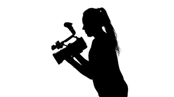 Der Videofilmer arbeitet mit einer professionellen Kamera. weiß. Silhouette