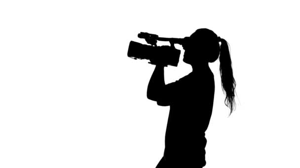 Girl shoots video or movie. White. Silhouette
