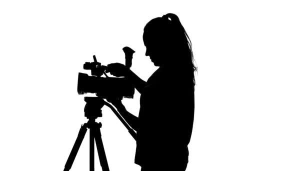 Mädchen fixiert die Kamera auf einem Stativ. weiß. Silhouette