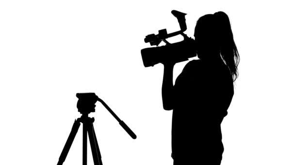 Mädchen mit der Kamera in der Hand ist im Studio. weiß. Silhouette