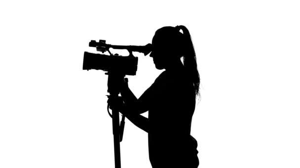 Bediener bewegt die Kamera. Videografie im Atelier. weiß. Silhouette