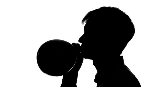 Man is blowing a balloon. Silhouette. Close up. White