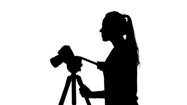 Fotograf pracuje se stativu. Bílé. Silueta