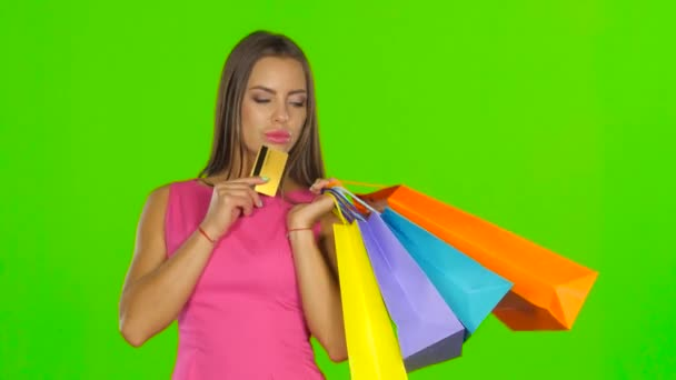 Woman with shopping bags and credit card. Green screen. Close up