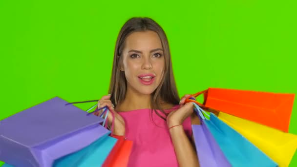 Woman holding shopping bags and smiling. Green screen. Close up