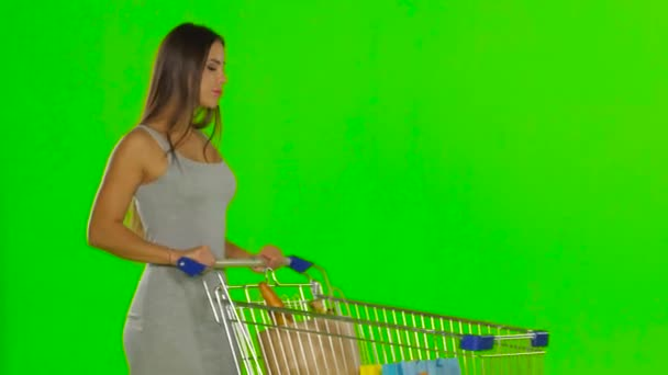 Woman pushing a cart with food. Green screen