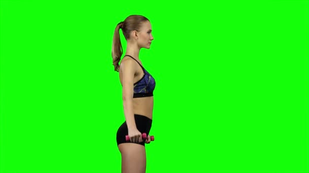 Girl with dumbbells in profile. Green screen