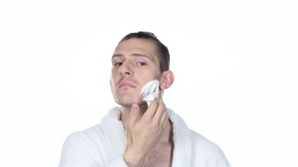 Uomo che applica la schiuma da barba. Capelli legati in panino. Priorità bassa bianca