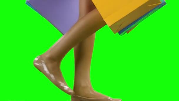 Žena držící nákupní tašky a chůzi. Zelená obrazovka