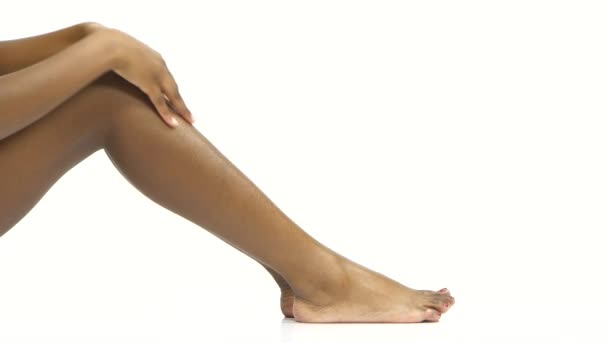 Woman gently touching her leg. White. Close up