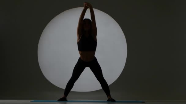 Žena se ohýbá tělo na fitness. Zadní světlo. Silueta
