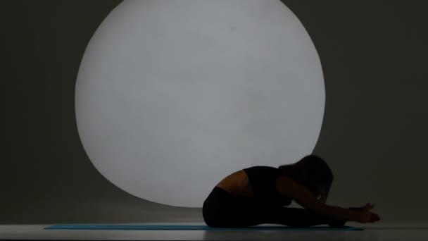 Atlet tom rozdělení ležící na zádech. Zadní světlo. Silueta