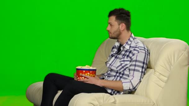 Muž, sledování televize a usmívá se. Zelená obrazovka