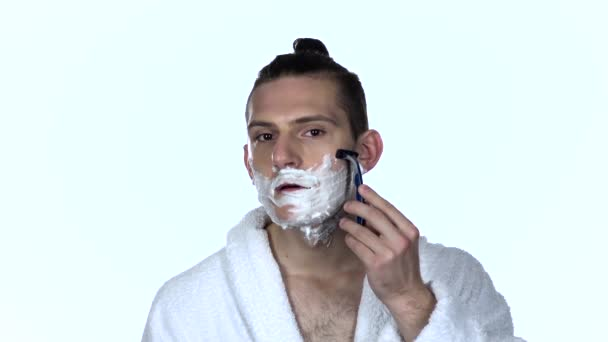 Guy makes mornings procedure and shaving. White background. Slow motion