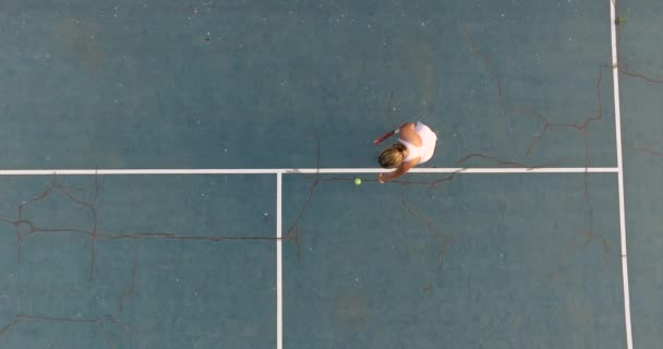 Professional tennis player taking the tennis ball and serving. Overhead shot