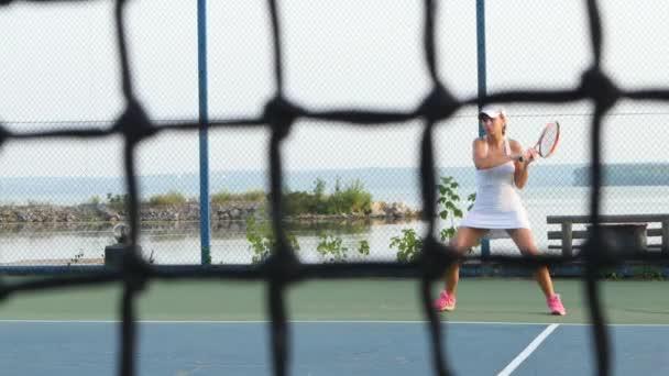 Na tenisovém hřišti hraje dívka venkovní tenis. Dolly