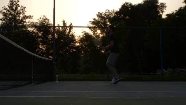 Muži hrají tenis při západu slunce