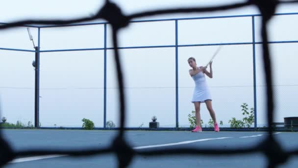 Tennis player volleys using forehand technique. Tennis net in front. Outdoor courts