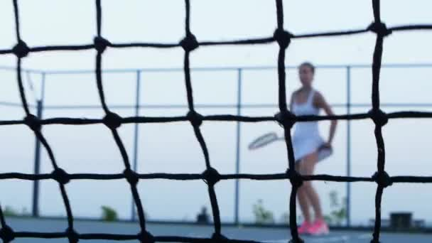 Tennis ball hits net. Tennis player in the background