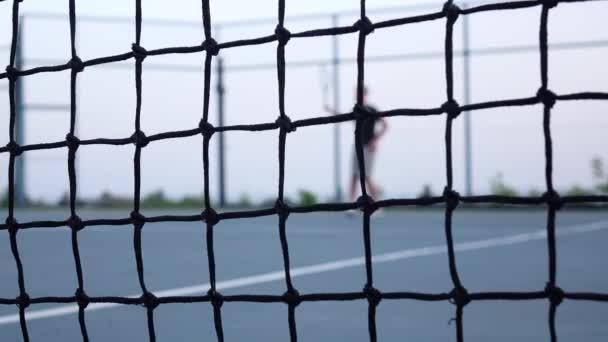 Tenista salvy forhend technikou. Tenisová síť vpředu. Dolly zastřelil