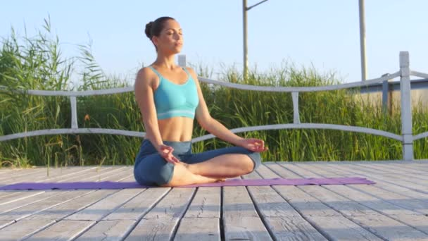 Healthy woman meditating in pose lotus over on purple rug