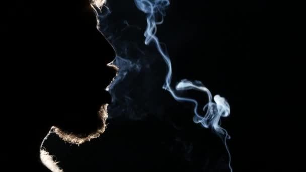 Mann raucht Zigarre. nimmt einen großen Zug und pustet Rauch. Schwarzlicht. Silhouette. Nahaufnahme