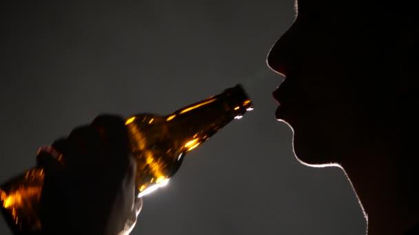 Člověk pije pivo z láhve. Šedá. Zblízka