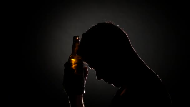 Drunk man drinks beer from a bottle. Grey. Close up