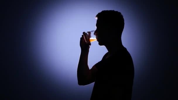 Alcohol addiction. Man drinking whiskey. Back light