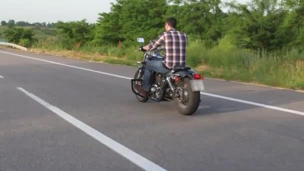 Muž na motorce jezdí na silnici. Záběrů