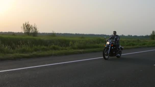 Muž na motorce jezdí, při západu slunce. Záběrů