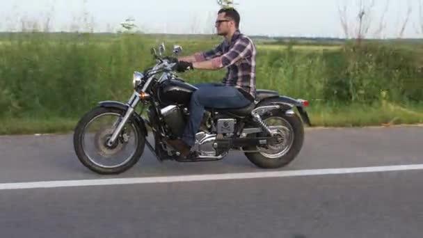 Muž v brýlích jezdí na motorce a se těší. Záběrů