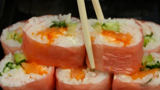 Chef puts sushi in pink norrie in a bowl. Close up