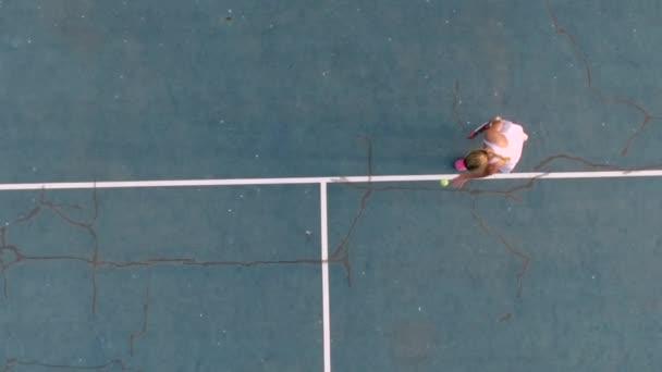 Holka servírovává tenisovou kouli. Zpomaleně